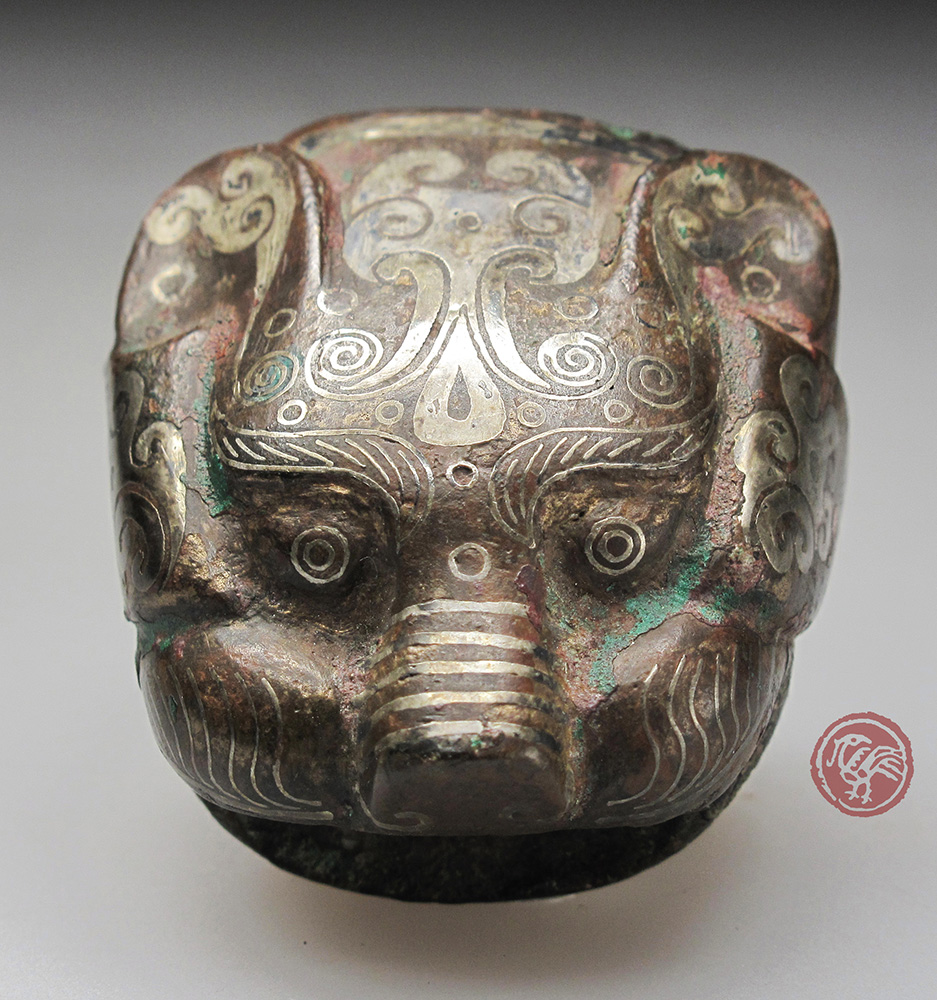 ARCHAIC BRONZE FITTING SHAPED AS A TIGER HEAD WITH SILVER INLAID